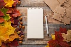 与笔的空白的白色笔记薄和在老木背景的秋叶 看板卡问候万圣节 顶视图 库存图片