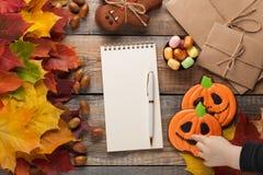 与笔的空白的白色笔记薄在万圣夜胶粘的糖果、南瓜和姜饼曲奇饼o的秋叶背景和糖果 库存照片