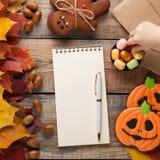 与笔的空白的白色笔记薄在万圣夜胶粘的糖果、南瓜和姜饼曲奇饼o的秋叶背景和糖果 免版税图库摄影