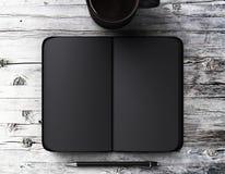 与笔的空白的黑日志和一杯咖啡在一张木桌上的 免版税库存照片