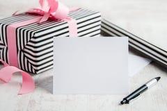 与笔的空的贺卡 被包裹的礼物和包装纸卷在背景中 免版税库存照片