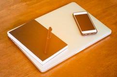 与笔的老笔记本与在木书桌上的手机和片剂个人计算机 太阳光 免版税库存图片