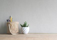 与笔的仙人掌在持有人篮子的花和铅笔在木桌上 免版税库存照片
