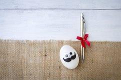 与笔礼物的滑稽的鸡蛋在黑森州的织品 库存照片
