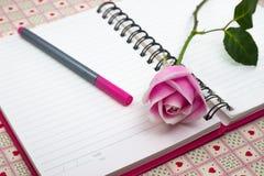 与笔记和铅笔的桃红色玫瑰 图库摄影