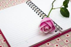 与笔记和铅笔的桃红色玫瑰 库存照片