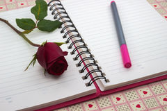 与笔记和铅笔的红色玫瑰 免版税图库摄影