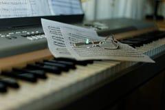 与笔记和玻璃的钢琴 免版税库存图片