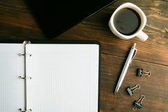 与笔记本、咖啡和笔记薄的企业概念在棕色木头 免版税图库摄影