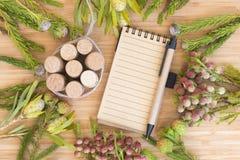 与笔记本、花和酒黄柏的一幅静物画 免版税库存照片