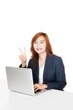 与笔记本个人计算机的亚洲女勤杂工展示胜利标志 免版税库存照片