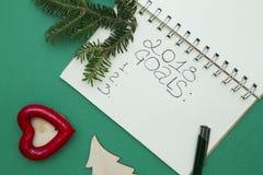 与笔记本和一个云杉的分支的绿色圣诞节或新年背景 库存照片