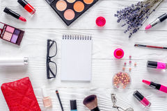 与笔记本和淡紫色顶视图嘲笑的化妆用品构成 库存图片