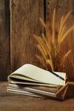 与笔记本和花狐尾的静物画在木背景除草 免版税库存照片