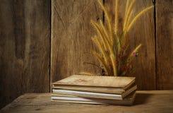与笔记本和花狐尾的静物画在木背景除草 库存照片