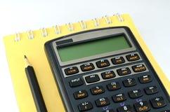 与笔记本和铅笔的财务计算器 免版税图库摄影