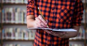 与笔记本的大学生中间部分反对模糊的书架 免版税库存图片