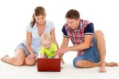 与笔记本的愉快的家庭。 库存照片