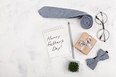 与笔记本的愉快的父亲节背景,礼物、玻璃、领带和bowtie在白色台式视图在舱内甲板放置样式 库存图片