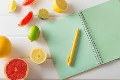 与笔记本的柑橘在木桌上 免版税库存图片