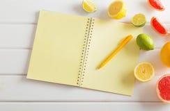 与笔记本的柑橘在木桌上 免版税库存照片
