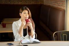 与笔记本的美丽的微笑的年轻亚裔女实业家饮用的咖啡在咖啡馆的桌上 免版税图库摄影