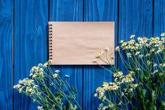 与笔记本的花卉现代设计在蓝色木桌面看法嘲笑 图库摄影
