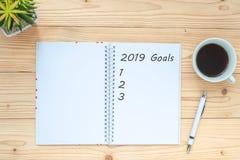 与笔记本的2019个目标、无奶咖啡杯子、笔和玻璃在桌上,顶视图和拷贝空间 新年新的开始,决议,如此 免版税库存照片