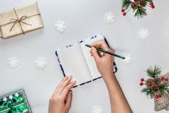 与笔记本,女性的圣诞节构成递绿色铅笔小盒子、雪花和云杉的分支红色莓果 免版税图库摄影