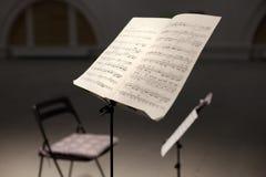 与笔记的在阶段的乐谱架和椅子 免版税图库摄影