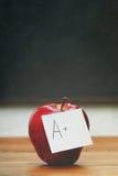与笔记的红色苹果关于有黑板的书桌 免版税库存图片