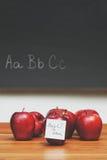 与笔记的苹果关于有黑板的书桌在背景中 免版税库存照片