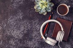 与笔记薄、耳机和咖啡的表 库存照片