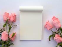 与笔记薄和玫瑰的平的位置在白色背景 与文本地方的浪漫横幅模板 免版税库存图片