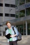 与笔记薄的微笑的大学生常设外部 免版税库存照片