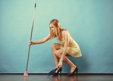 与笤帚的端庄的妇女详尽的地板 免版税库存照片