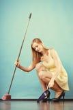 与笤帚的端庄的妇女详尽的地板 库存照片