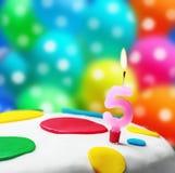与第五的灼烧的蜡烛在生日蛋糕 免版税库存照片