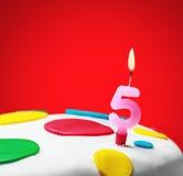 与第五的灼烧的蜡烛在生日蛋糕 免版税图库摄影