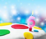 与第五的灼烧的蜡烛在生日蛋糕 库存图片