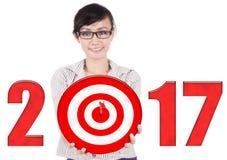 与第的女性举行的掷镖的圆靶2017年 免版税库存照片