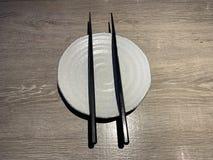 与筷子的白色日本盘在木桌上 库存图片