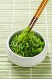 与筷子的辣海草沙拉在竹背景 免版税库存图片