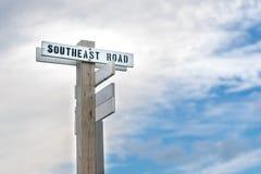 与简单的黑白路牌的老木路标,指明道路东南路,石块海岛,RI 库存图片