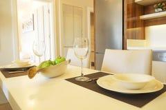 与简单的minimalistic现代室内设计的美丽的太阳边公寓,开放学制厨房客厅在阳光下 库存图片