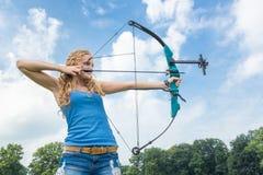 与箭头和复合弓的白肤金发的白种人女孩射击 免版税库存图片