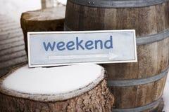 与箭头的木标志在树桩与词周末 免版税库存图片