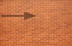 与箭头的现代红砖墙壁难看的东西背景在砖墙上 免版税库存图片