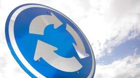 与箭头的蓝色路标在反对天空的一个圈子 免版税图库摄影