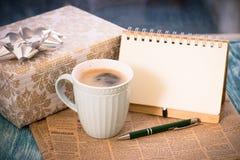 与箱子、杯子、笔记本和笔的镭欢乐静物画 免版税库存照片
